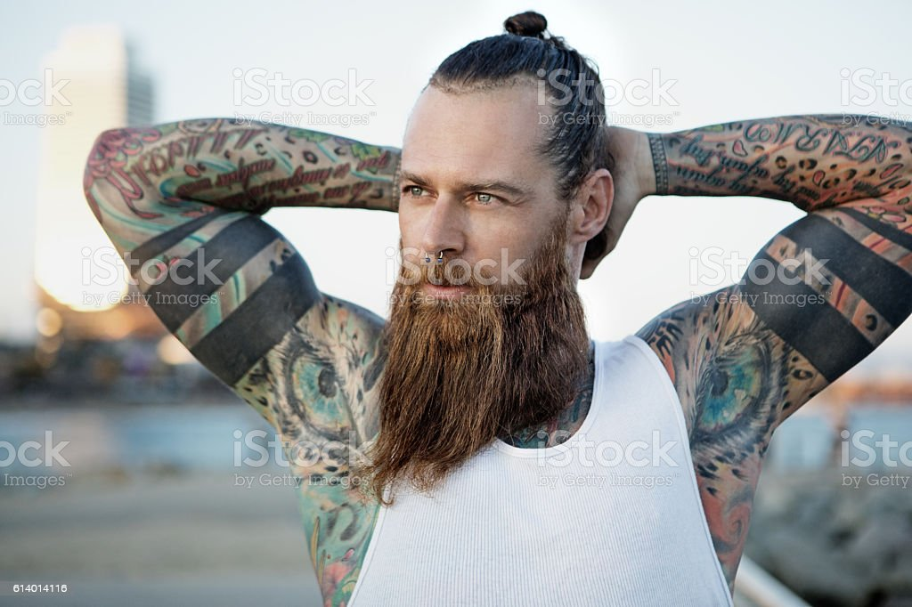 Heavily tattooed bearded athletic alternative man stretching before a workout stock photo