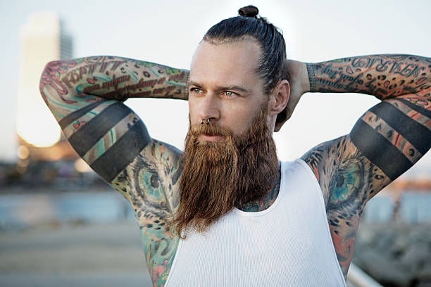 Heavily tattooed bearded athletic alternative man stretching before a workout - foto stock
