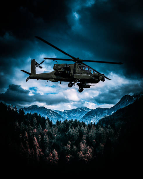 Heavy armed attack helicopter flies over hills stock photo