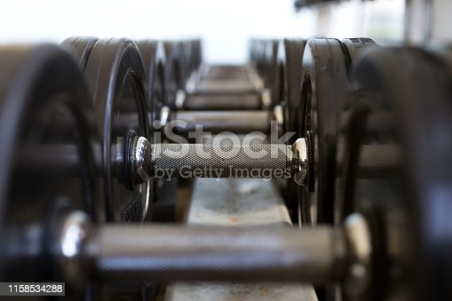 Heavy black metal dumbbells lying in a row, closeup