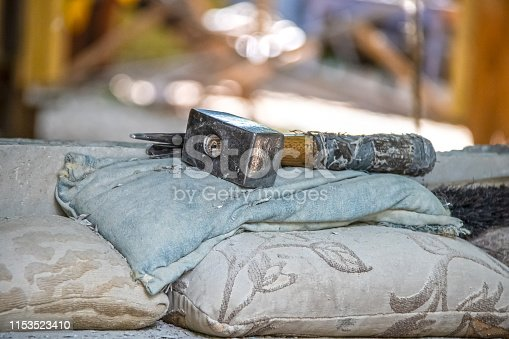 547224670istockphoto Heavy blacksmiths hammer with handle wrapped in rags lays on old pillows and cloth in an old-fashioned blacksmiths shop with blurred bokeh background 1153523410
