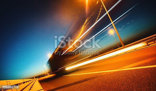 Closeup side view of a white cargo truck driving on a highway at late sunset. The truck is lit by street lights and motion blurred while the sky is lit by blue hour extravaganza.