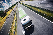 Closeup top view of a white green cargo truck driving on a highway.  It's sunny summer day and the road is clear. Tilt shot, copy space.