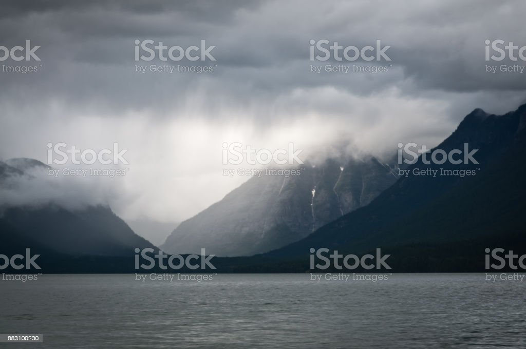 Heavy clouds over a mountain lake stock photo