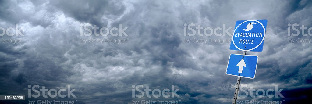 Heavy clouds with hurricane evacuation route blue sign stock photo