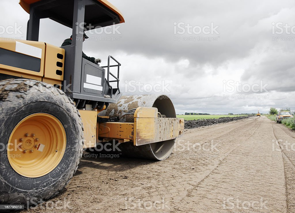 Heavy construction equipment preparing surface for a new road royalty-free stock photo
