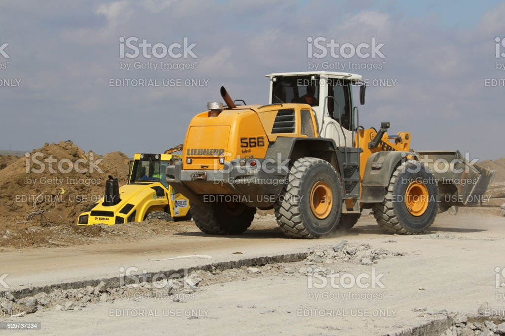 Heavy construction equipment working on a runway construction site as...