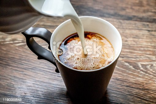 Heavy cream being poured into a cup of hot fresh coffee