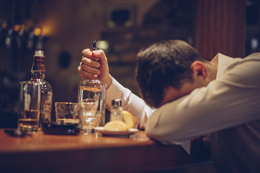 One man, sitting at the bar counter alone, he has drinking problems, sleeping on bar counter.