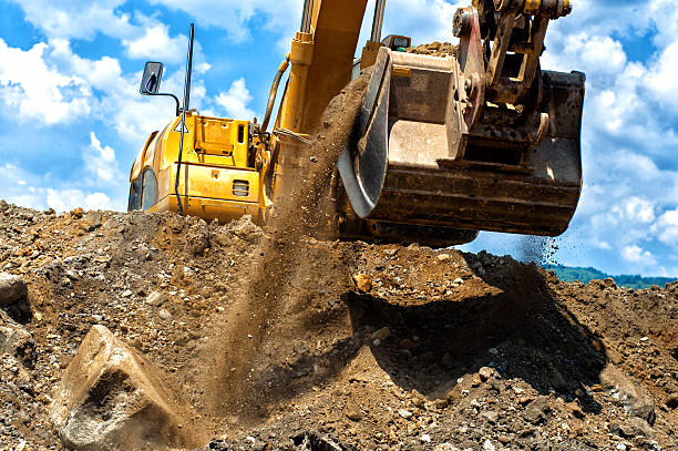 heavy duty construction excavator moving earth and sand stock photo