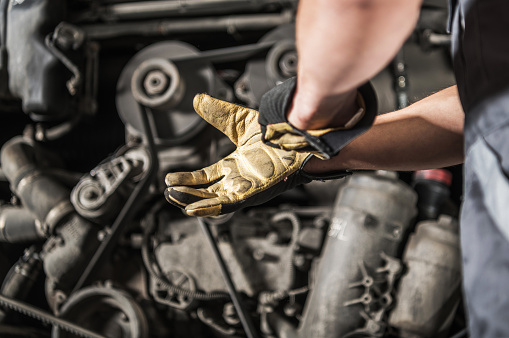Caucasian Heavy Duty Diesel Engines Mechanic Preparing For Work Wearing Safety Gloves
