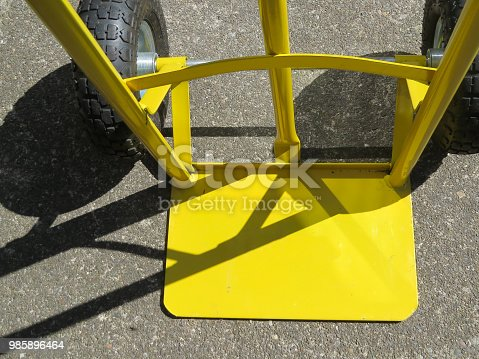 Heavy duty empty yellow sack barrow with shadows viewed from above. Close up.