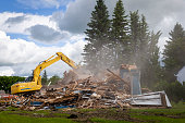 horizontal image of a yellow  heavy duty  machinery tearing down and demolishing a wooden residental building with dust flying into the air at daytime in the summer.