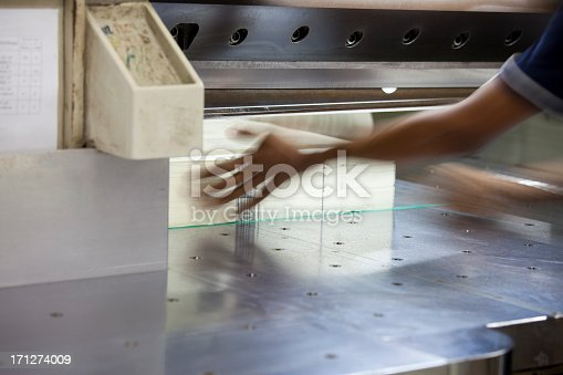Books being trimmed with a heavy duty paper guillotine at a printing factory. Motion blur on the hands, selective focus.