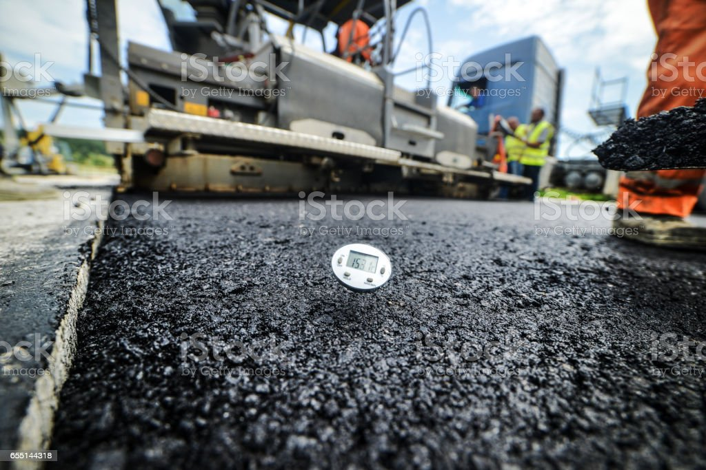 Heavy duty road building. Hot Asphalt being laid stock photo