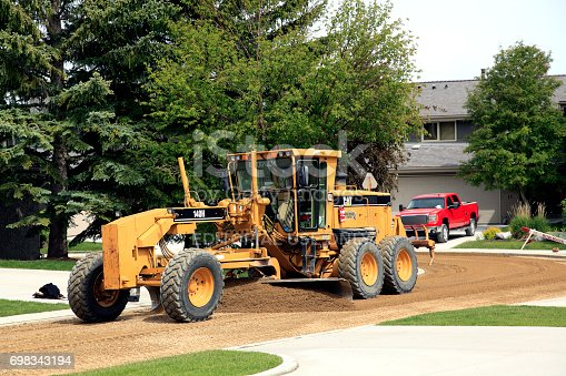 Calgary,Alberta ,Canada- June 19,2017: Large Caterpillar equipment smoothing and grading the cul -de- sac in a residential area prior to asphalt. Red truck in driveway at rear.