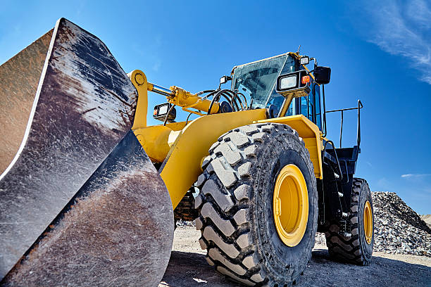 Heavy equipment machine wheel loader on construction jobsite Construction heavy equipment loader and bucket on jobsite construction machinery stock pictures, royalty-free photos & images