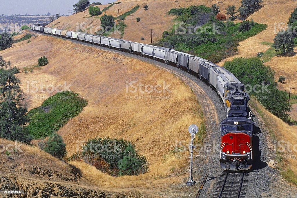 Heavy grain train climbing through hills stock photo