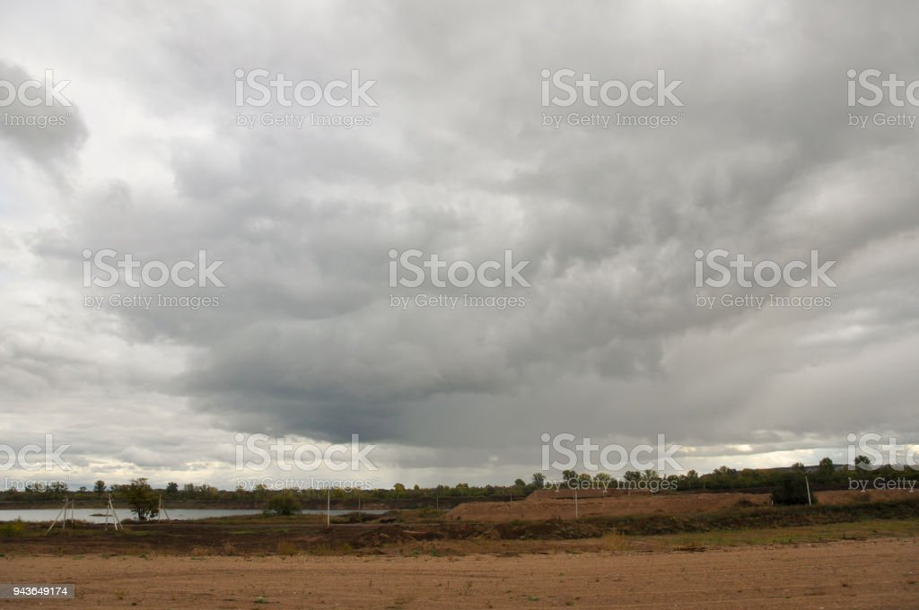 Heavy grey clouds in the cold autumn sky over rivers, fields, forests and mountains stock photo