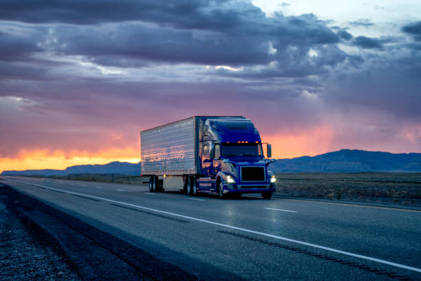 Heavy Hauler Semi-Trailer Tractor Truck Speeding Down a Four-Lane Highway with a Dramatic and Colorful Sunset or Sunrise In the Background stock photo