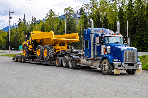 Big truck with a low platform trailer carrying a tipper truck on a public parking area of a truck stop