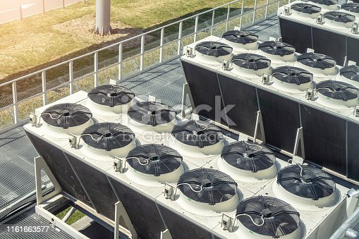 912000730 istock photo Heavy heating ventilation cooling and air conditioning set system on roof top of big industrial building 1161663577