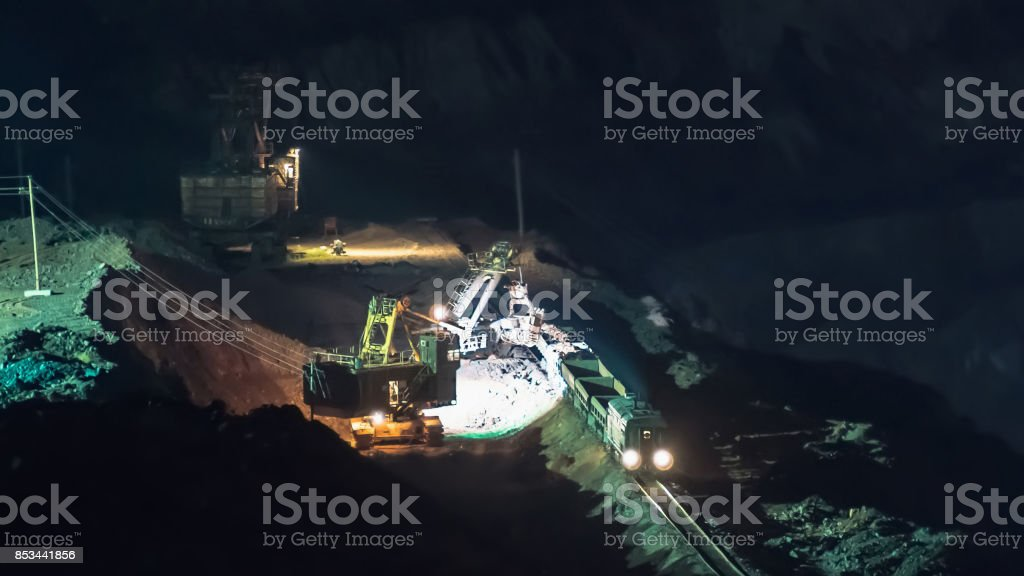 Heavy industry machines at dusk working in open pit mine stock photo