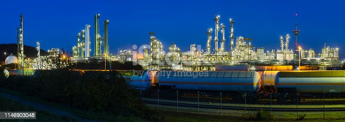 Panoramic view of a chemical plant and refinery with night blue sky and illumination, some freight trains in the foreground.