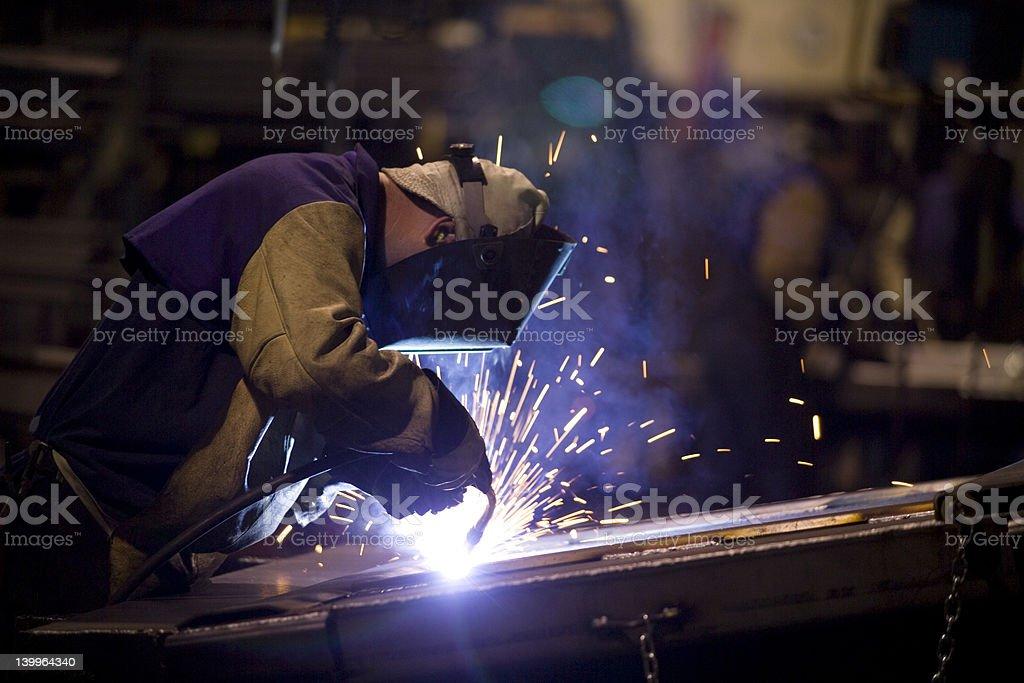Heavy industry weldor at work on factory floor.