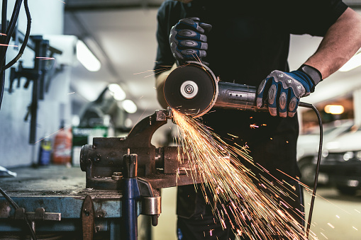 Heavy industry worker cutting steel with an angle grinder.  ( Industry concept )
