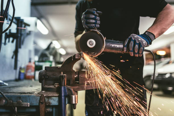 Heavy industry worker cutting steel with an angle grinder. stock photo