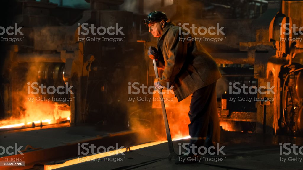 Heavy Industry Worker Doing Quality Control in Foundry. Rough Industrial Environment. Wide Shot. stock photo