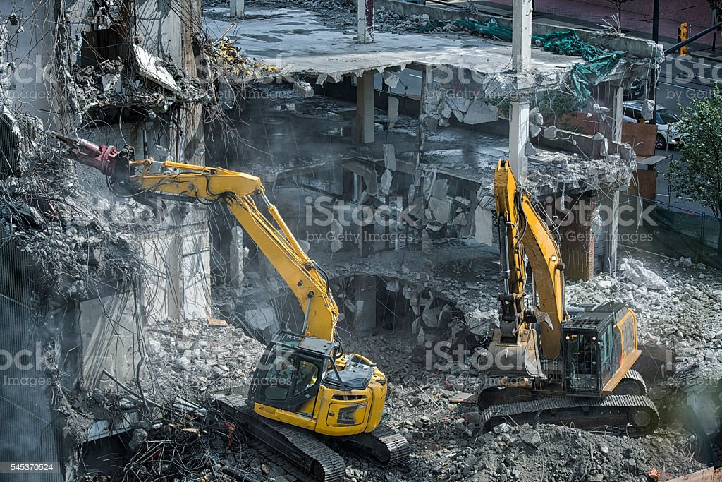Heavy machinery taking down an old building stock photo