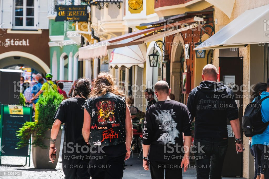 Heavy Metal fans metalheads walk in the street seen from behind - Alternative music lifestyle stock photo