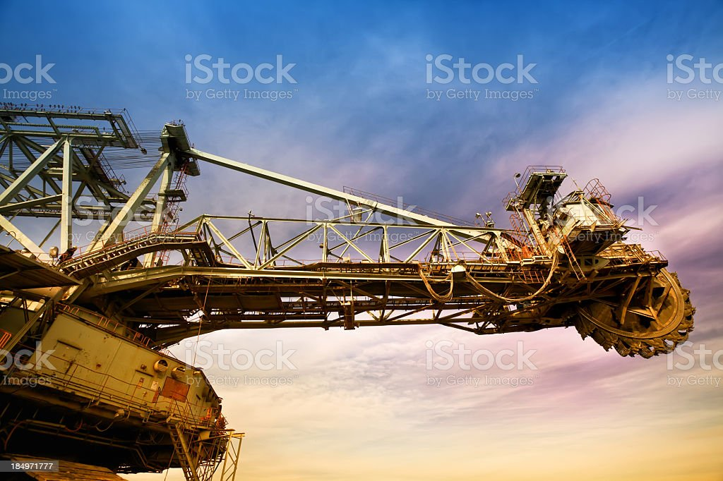 Heavy mining drilling machine against a colorful sky stock photo