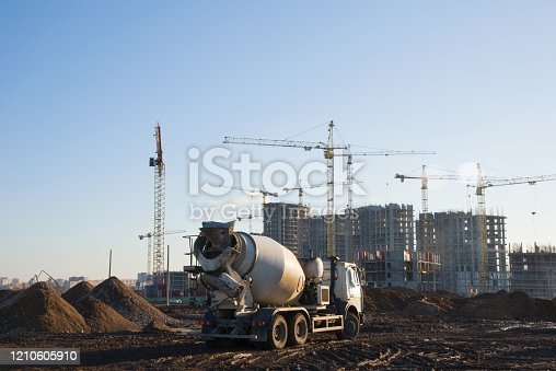 Heavy mixer concrete truck waiting for to be loaded concrete at a construction site. Tower cranes constructing a new residential building.