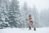 Active pregnant woman in underware ski mountaineering in snowfall morning