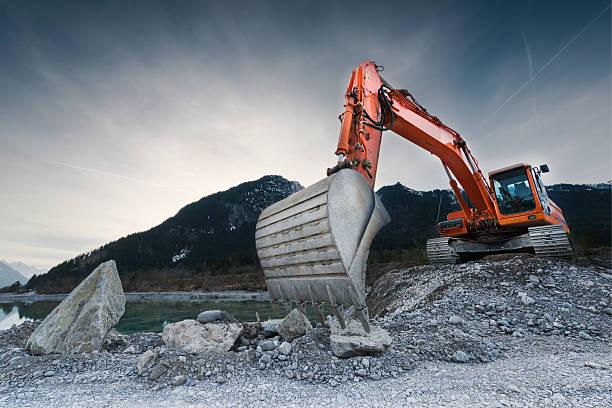 heavy organge excavator with shovel standing on hill with rocks - excavator bildbanksfoton och bilder