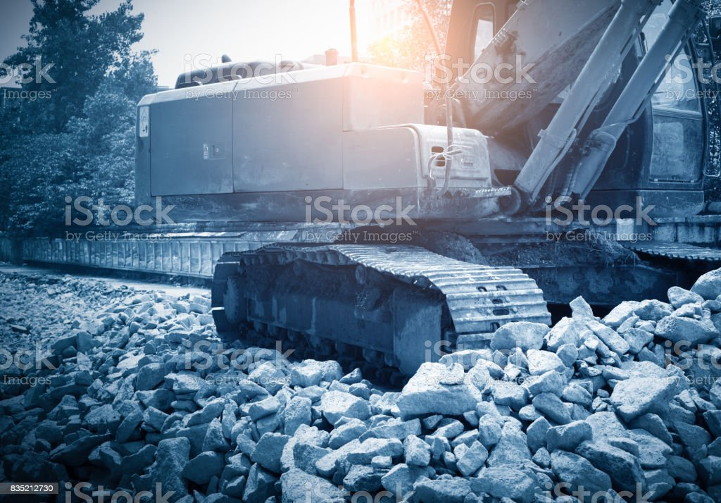 heavy organge excavator with shovel standing on hill with rocks stock photo
