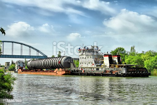 istock Heavy oversized chemical apparatus is transported by river transport through the shipping channel on a special barge 1138867869