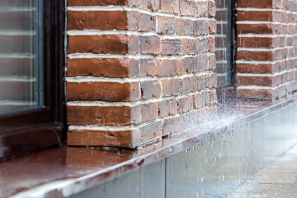 heavy rain pouring on pavement on brick wall background stock photo