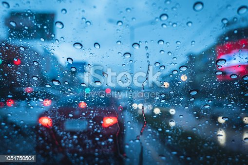 1054750504 istock photo Heavy raining strom when drive at evening blue chill wet windshield 1054750504