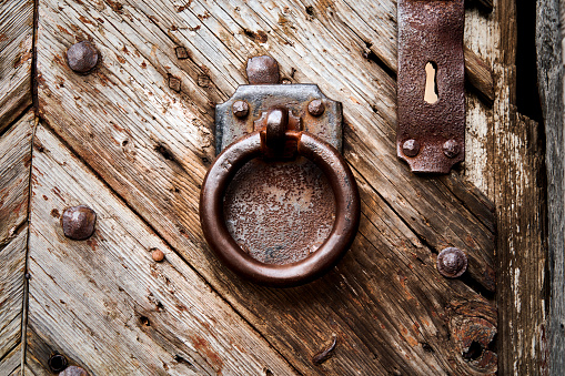 Heavy rusty iron door knocker, ring in front of rectangular iron plate on weathered grained massive old wooden door at the entrance of castle complex