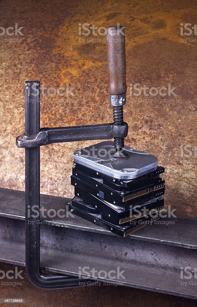 heavy screw clamp giving pressure to several hard drives royalty-free stock photo