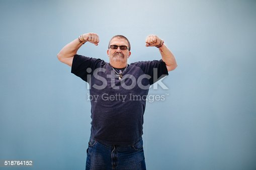 istock Heavy set older man showing his muscles 518764152
