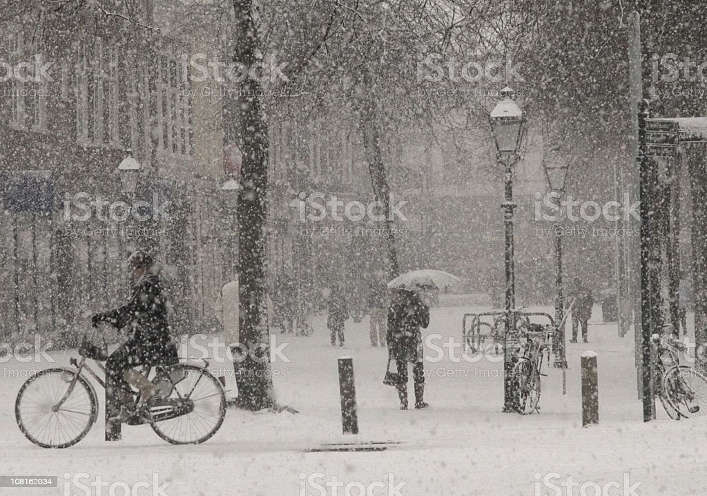 Heavy Snow Falling in Town Square with People Walking stock photo