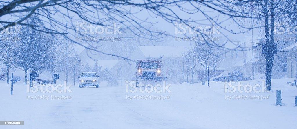 Heavy snowfall and a car behind  snowplow stock photo