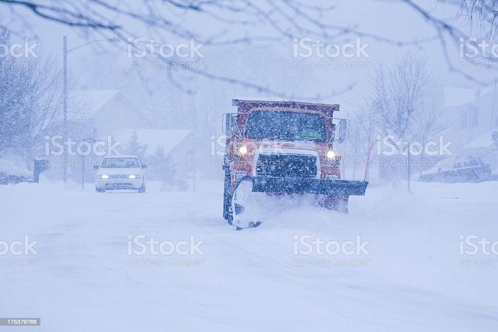 Heavy snowfall and a car behind the snowplow stock photo