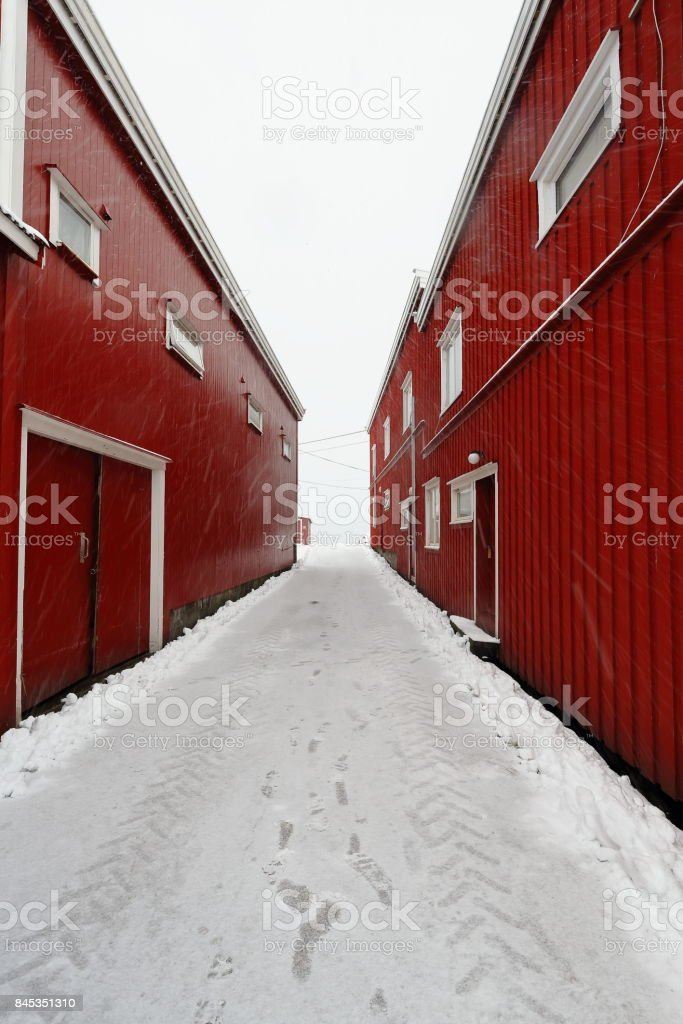 Heavy snowfall-tire tracks-narrow alley between red port warehouses. Hamnoy-Reine-Lofoten-Norway. 0396 stock photo