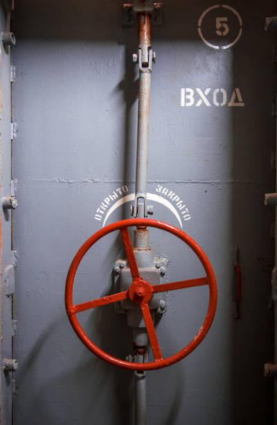 Heavy steel door with handweel Heavy steel door in the bomb shelter aegis stock pictures, royalty-free photos & images